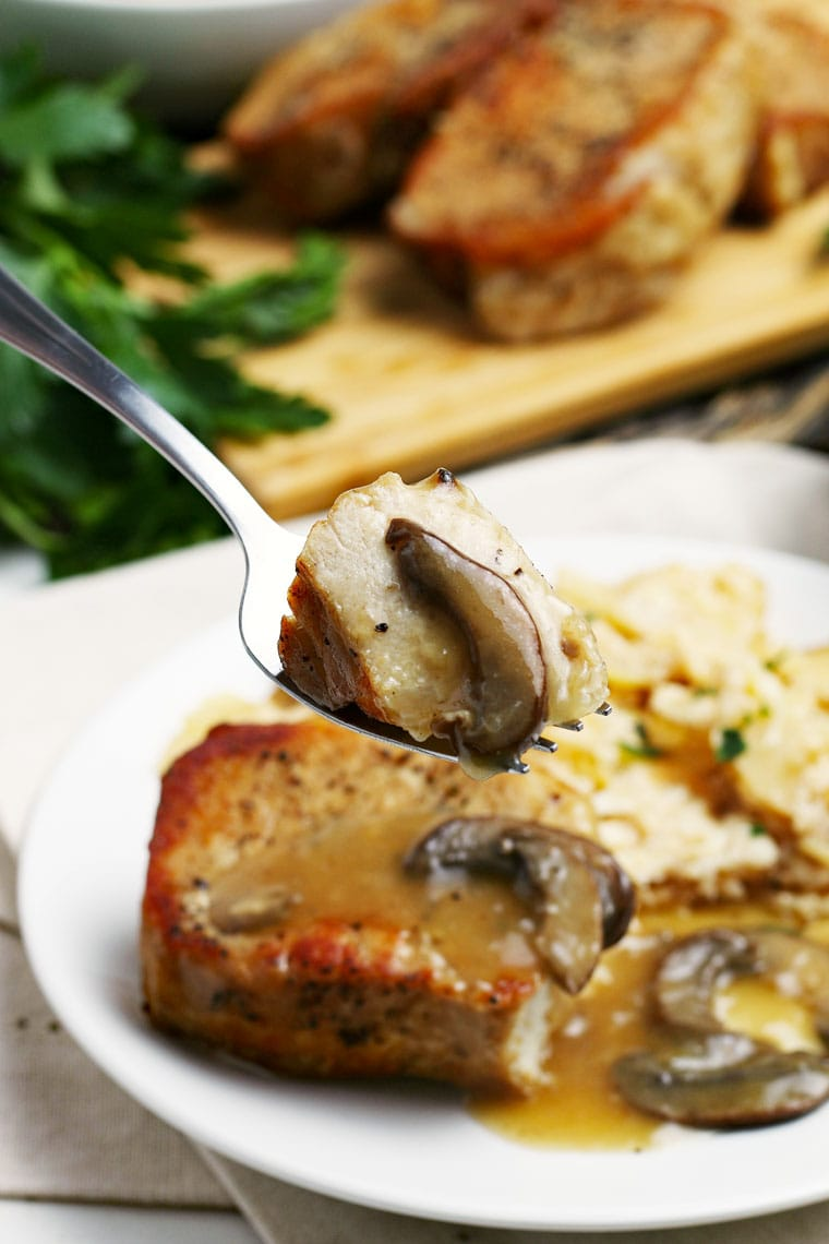 A plate and forkful of Instant Pot Pork Chops with mushrooms and potatoes with more pork chops on a cutting board in the background.