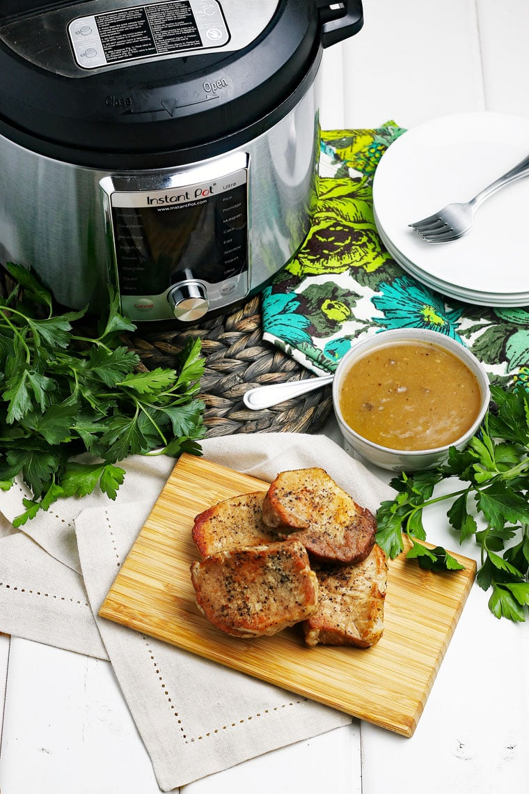 Pork chops on a wooden cutting board, a bowl of mushroom gravy, an Instant Pot on a woven mat, and white plates in the background.