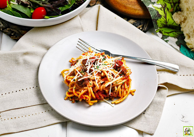 A plate of Instant Pot Spaghetti with cheese on a linen napkin with a bowl of salad.