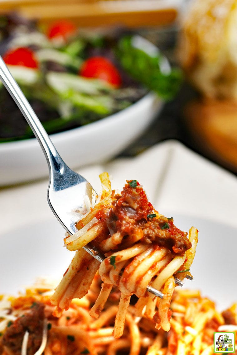 Closeup of spaghetti with meatsauce twirled around a fork with salad in a white bowl in the background.
