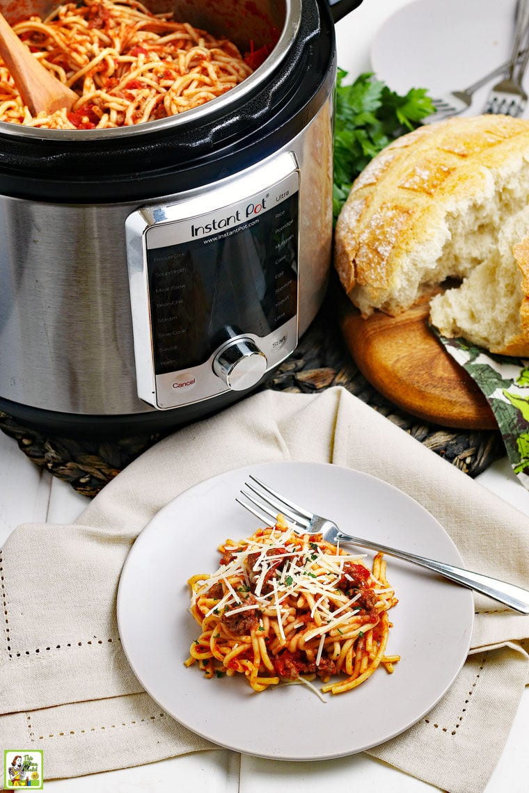 A white plate of spaghetti with meatsauce with a fork on a gray napkin with an Instant Pot of spaghetti with a wooden spoon, a loaf of crusty bread and a stack of plates in the background.