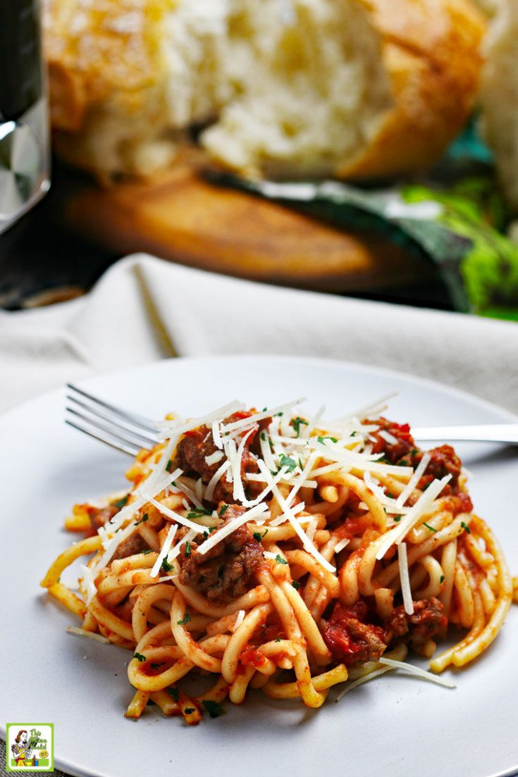 Closeup of a plate of spaghetti and meatsauce with a fork on a linen napkin with bread and a pressure cooker in the background.