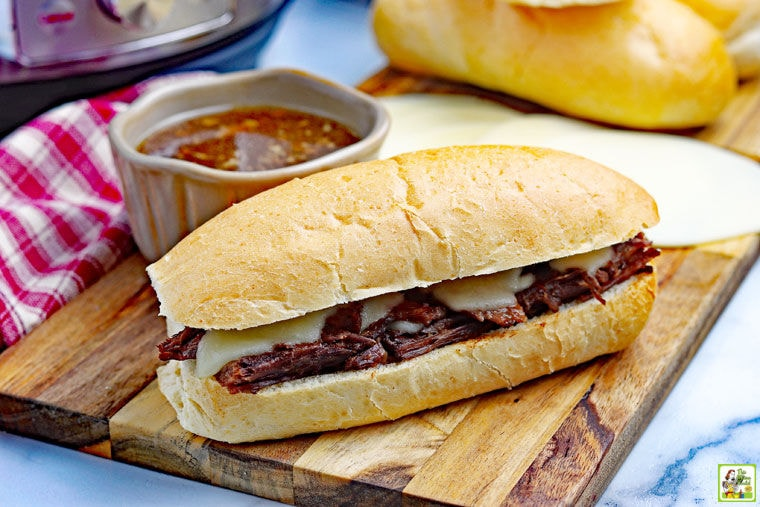 Instant Pot French Dip Sandwich with a bowl of au jus on a wooden cutting board with a napkin.