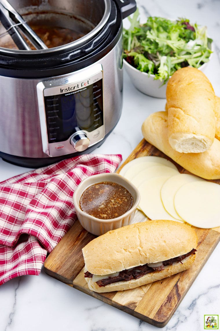 Overhead shot of a Instant Pot French Dip sandwich with bowl of au jus, red and white napkin, slices of cheese and bread rolls, an Instant Pot of French Dip, and a bowl of salad.