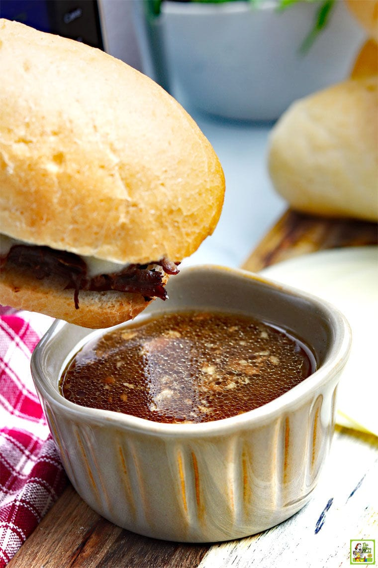 End of a Instant Pot French Dip Sandwich dipping into a ramekin of au jus.