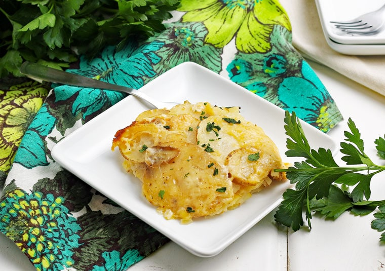 A white plate of Super Cheesy Crockpot Scalloped Potatoes with a fork on a floral napkin with fresh parsley.