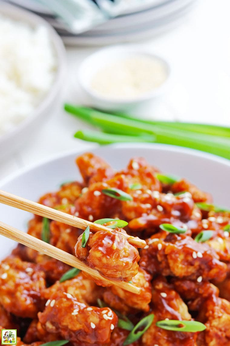 Close up of a piece of General Tso chicken being picked up out of a bowl with chopsticks.