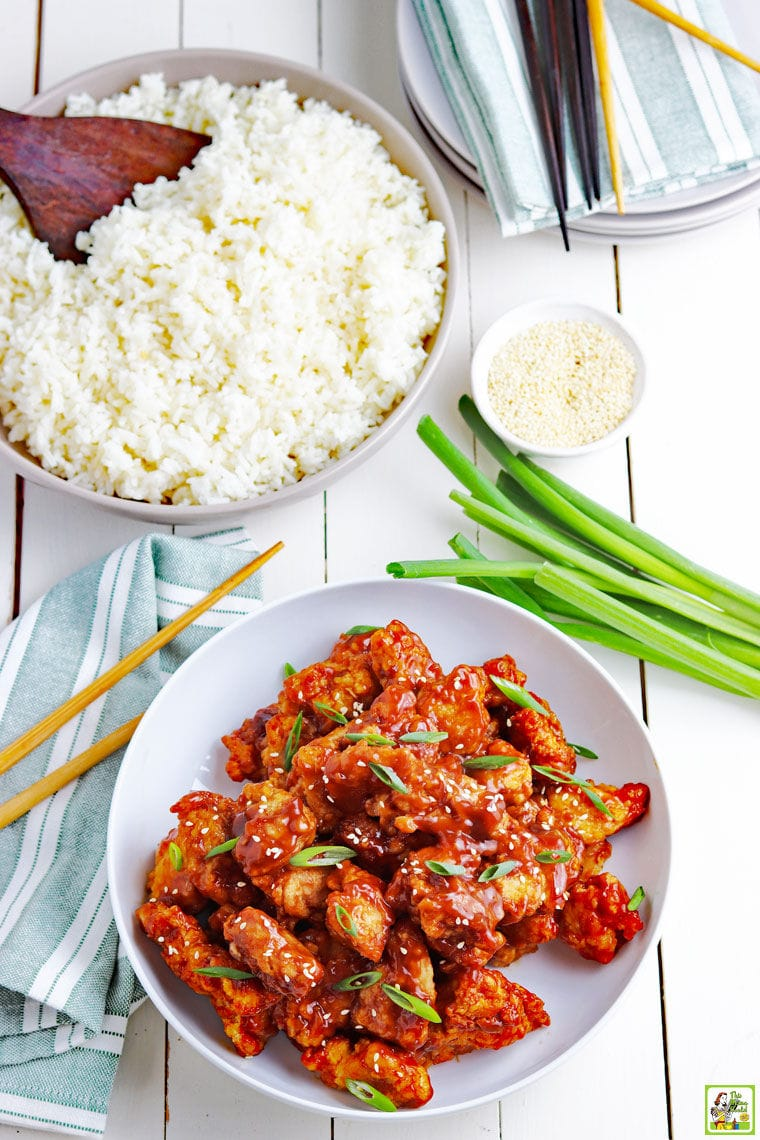 Overhead shot of a bowl of General Tso Chicken, a bowl of rice, green onions, chopsticks, napkins, and plates.