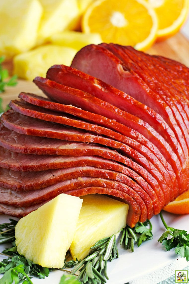 Closeup of a spiral cut Spiral Instant Pot Ham on a white ceramic platter with pineapple slices.