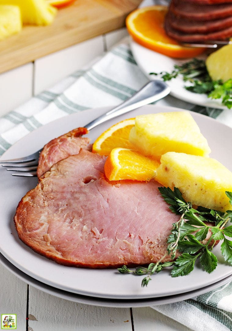 A slice of Instant Pot ham with orange and pineapple slices and herbs and a fork and napkin.