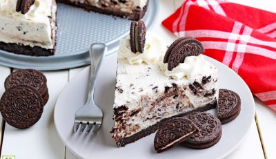 A plate of no bake Oreo cheesecake with a fork and a red napkin.