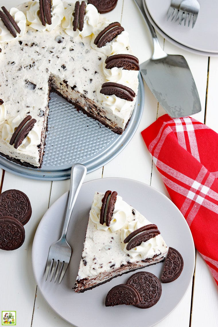 Overhead shot of a slice Oreo cheesecake on a plate with a Oreo cheesecake with a slice missing next to a cake server and a red cloth napkin.