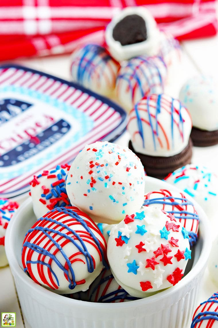 Red, white and blue Oreo cake balls in a bowl and with Oreos and holiday paperplates on a festive tabletop.