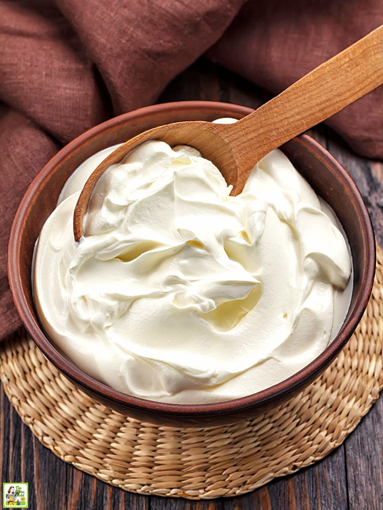 A brown bowl of sour cream with a wooden spoon and brown napkin.