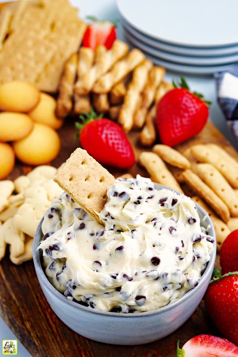A bowl of cookie dough dip recipe with a graham cracker with more dippers like cookies, crackers, and fruit and plates in the background.