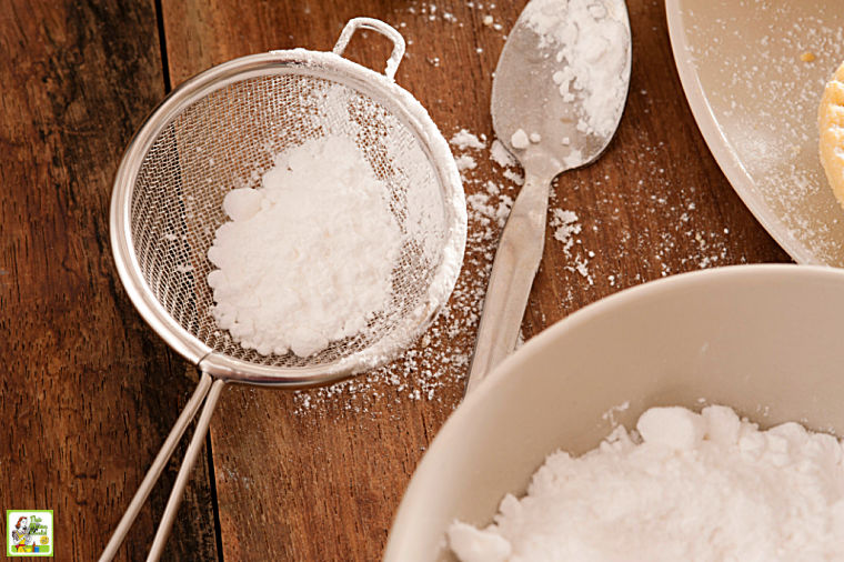 Fine mesh sieve, spoon and bowl filled with powdered sugar.