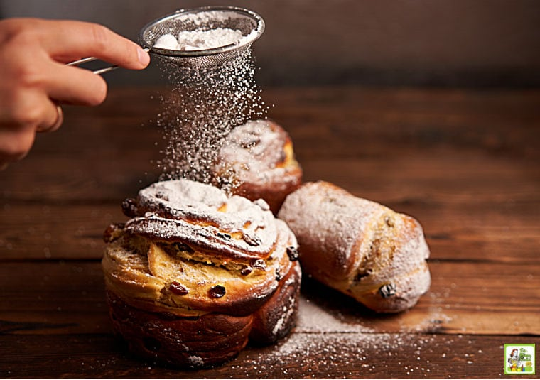 Hand sprinkling powdered sugar with a tea strainer over baked goods and pastries.