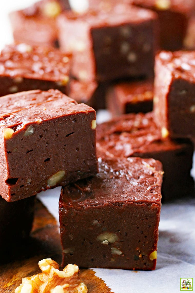 Pieces of chocolate and nut fudge on parchment paper.