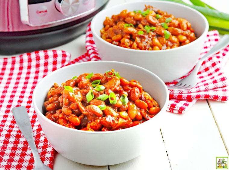 Two white bowls filled with Instant Pot Baked Beans on red and white checkered napkins with a fork and pressure cooker.
