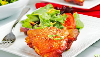 A piece of Instant Pot Chicken Thigh with Honey Garlic Sauce on a white plate with a fork, salad, and red napkin.