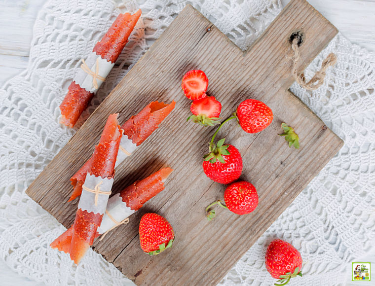 Strawberry Fruit Leather Roll-Ups on a wooden cutting board with strawberries.