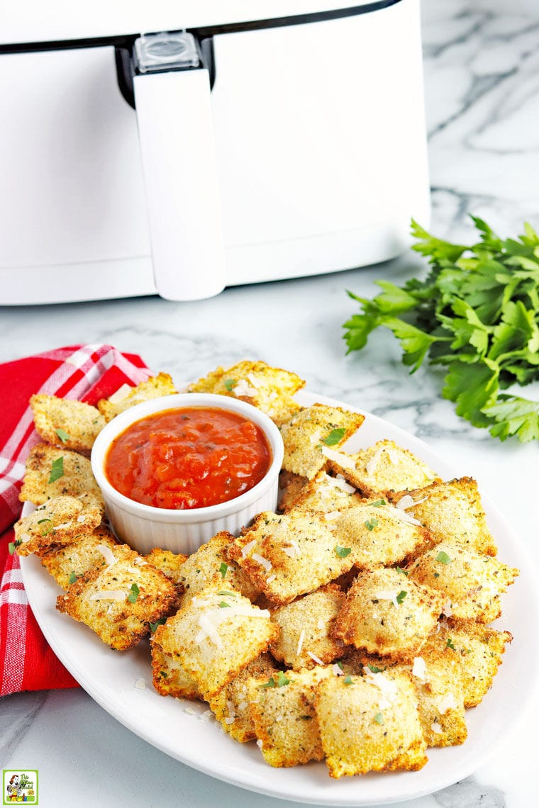 A platter of fried air fryer ravioli with dipping tomato sauce with napkin and an air fryer in the background.
