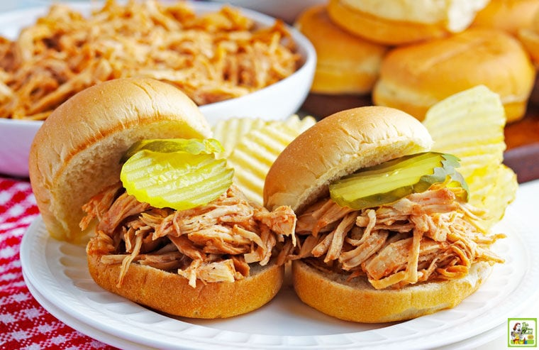 Two Instant Pot Pulled BBQ Chicken Sandwiches with pickles and potato chips on a white plate with bowl of shredded chicken and buns in the background.