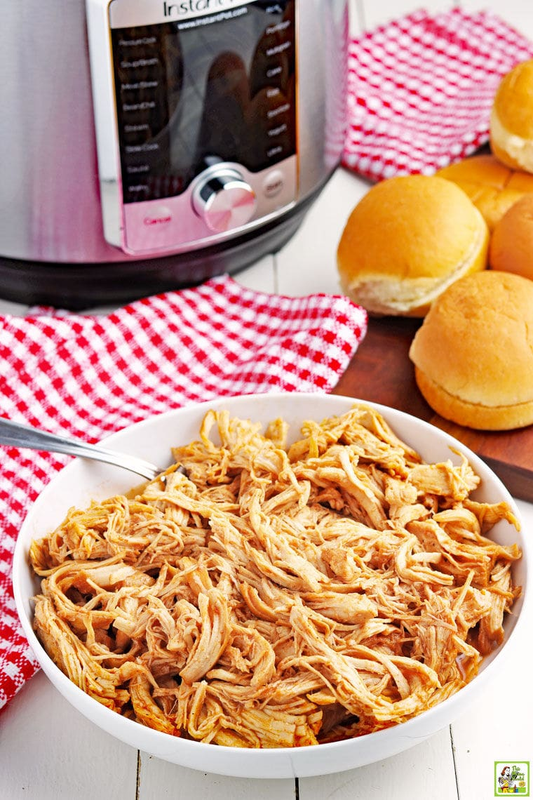 A bowl of shredded Instant Pot Pulled BBQ Chicken with fork, sandwich buns, red checkered napkins, and a pressure cooker.