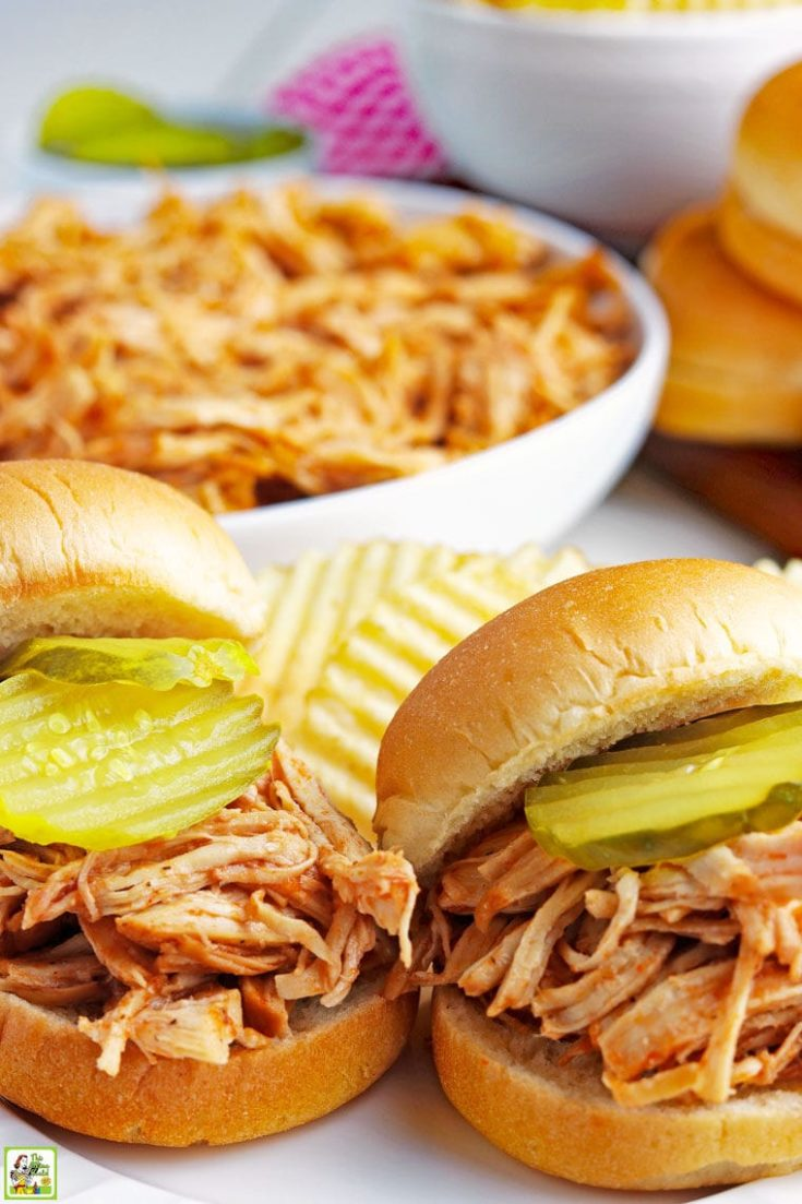 Closeup of shredded BBQ chicken sandwiches with pickles, potato chips, and a bowl of Instant Pot Pulled BBQ chicken.