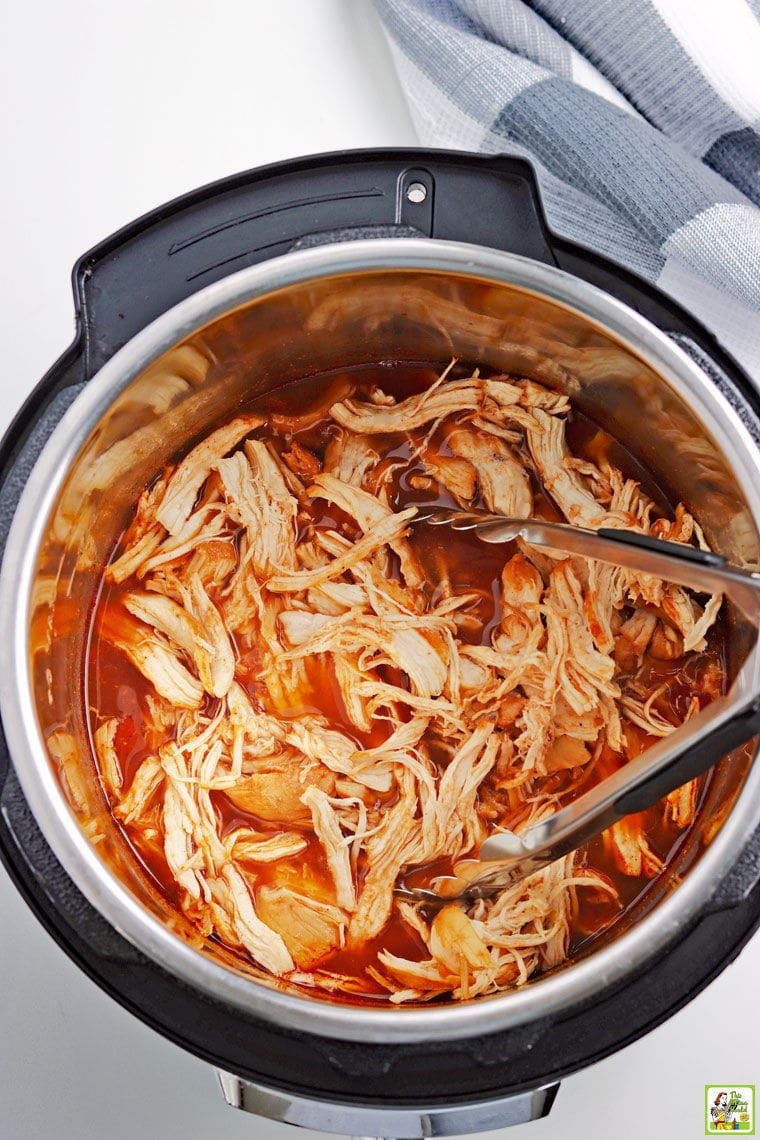 Overhead of Instant Pot Pulled BBQ Chicken with tongs in the open pressure cooker.