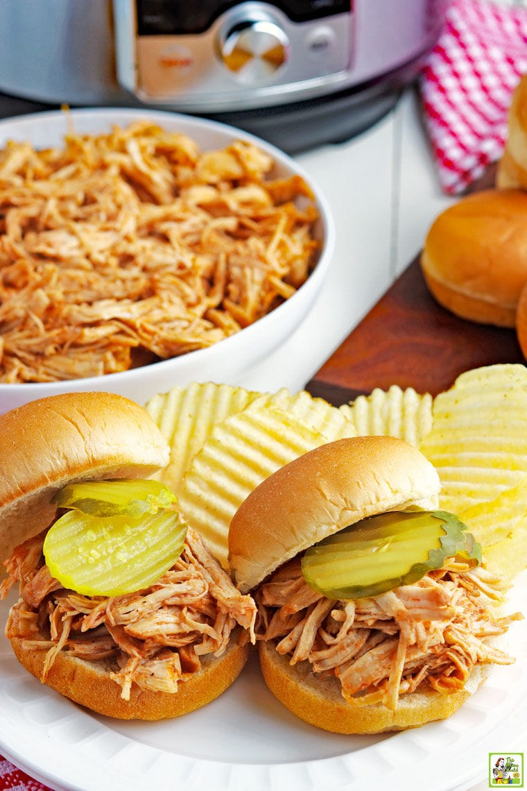 Two Instant Pot Pulled BBQ Chicken Sandwiches with potato chips on a white plate with a bowl of shredded BBQ chicken with a pressure cooker, sandwich buns, and a red checkered napkin.