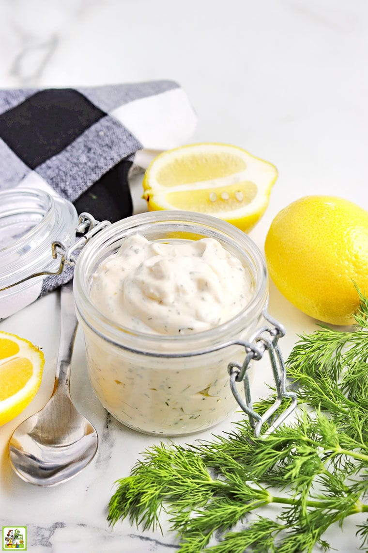 A glass jar filled with homemade tartar sauce, a bunch of fresh dill, lemons, a spoon, a whisk, and a black and white cloth napkin.
