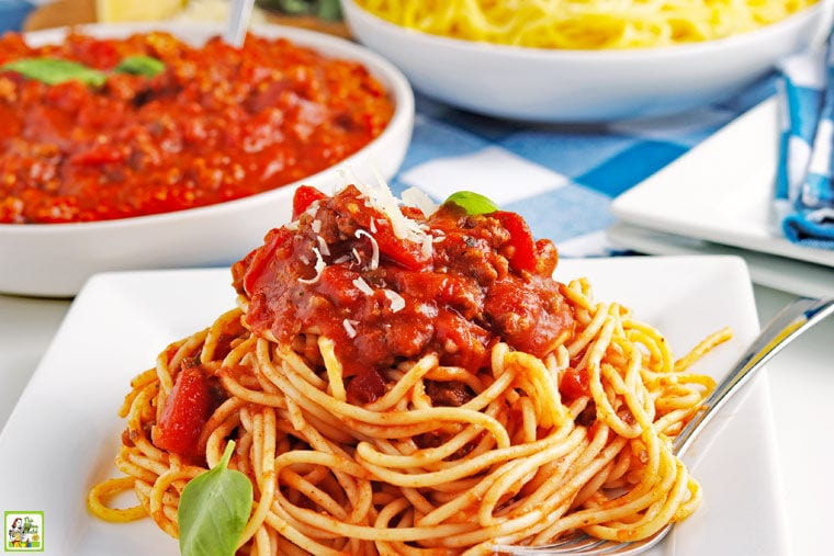 A white plate of crockpot spaghetti sauce on pasta with bowls of sauce and spaghetti in the background.