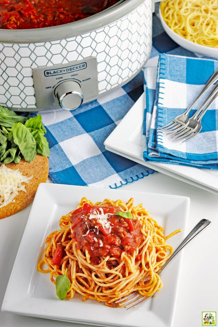 A white plate of crockpot spaghetti with meat sauce with blue and white napkins with plates and a slow cooker of sauce.