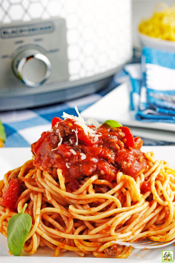 Closeup of a pile of slow cooker spaghetti sauce on pasta with a slow cooker and blue and white napkins in the background.