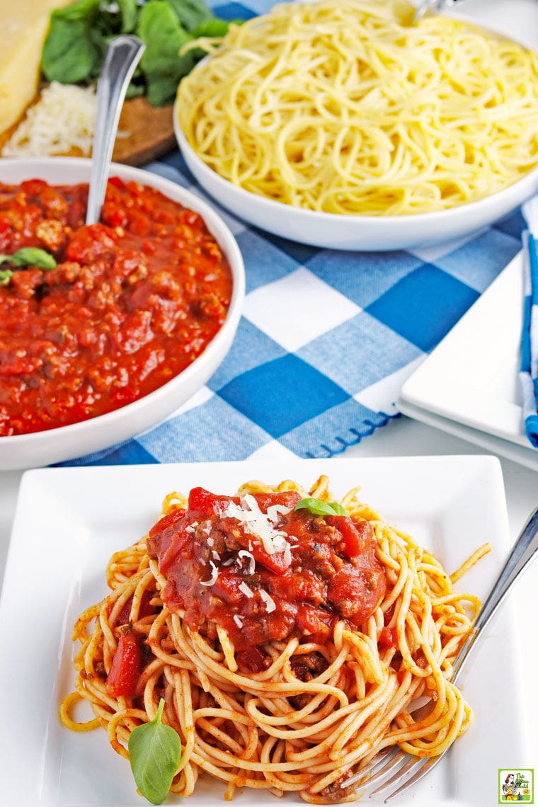 Overhead view of a plate of spaghetti sauce on pasta with bowls of crockpot spaghetti sauce and pasta with blue and white checked napkins.