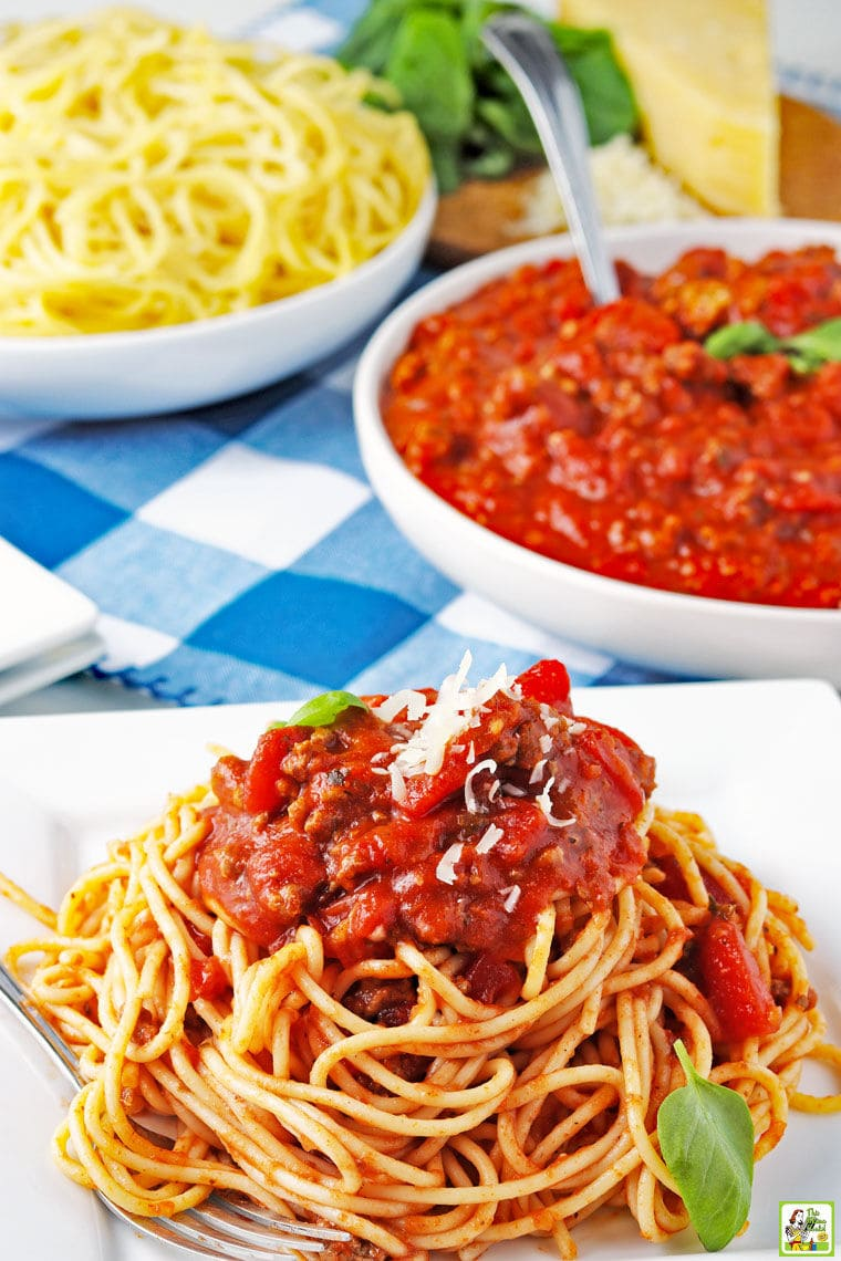 Closeup of a plate of slow cooker spaghetti sauce on a pile of spaghetti with bowls of sauce and spaghetti in the background.