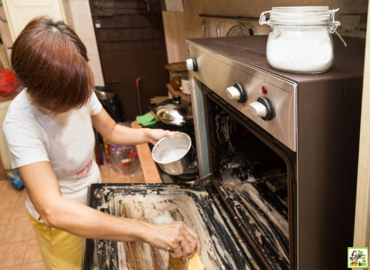 Woman brushing on baking soda paste in a dirty oven to clean it.