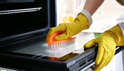 Woman wearing yellow rubber gloves cleaning oven with baking soda and scrub brush.