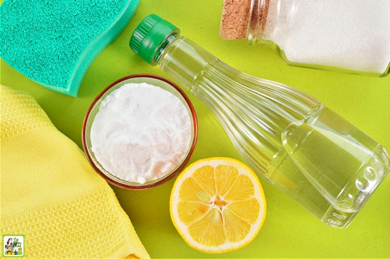 Materials for cleaning oven including baking soda, vinegar, lemon, salt, cleaning rags, and sponge.