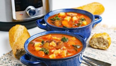 Two blue bowls of vegetable soup with bread, spoon, and an Instant Pot.